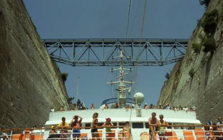 tourists on board watch as ship makes it way through the narrow canal