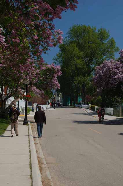 Pedestrians, both local and tourists, stroll down Huron Street on Mackinac Island