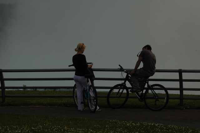 a biking couple is sihouetted by the mist of Horseshoe Falls