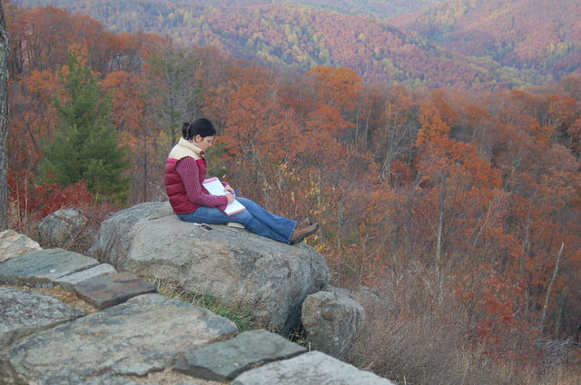 girl sits on rock overlooking hills
